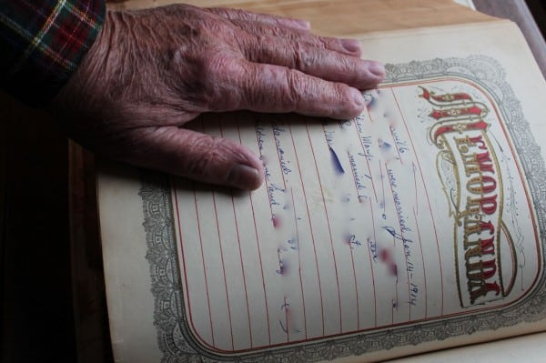 Dad rests hand on page with his name, names obscured